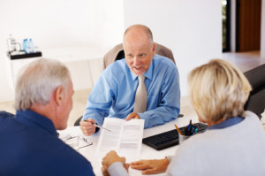Advisor advising couple with financial papers