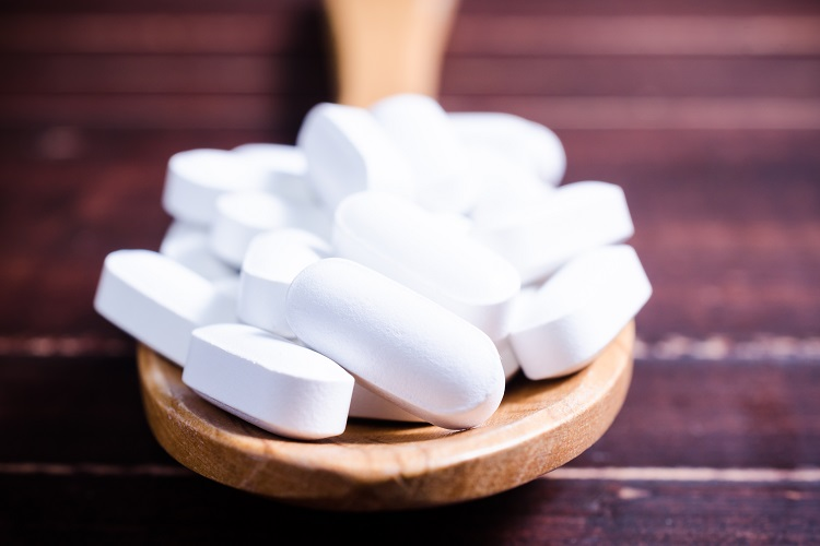 Close up white pills tablets on wooden spoon with wooden board background