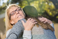 Two Ladies Hugging after sharing their Sobriety During the Holidays