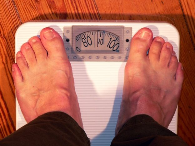 Man Concerned about His Weight Standing On A Weight Scale