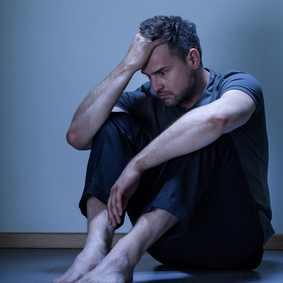 Portrait of depressed man sitting on the floor