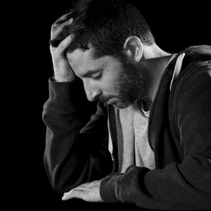 young desperate man suffering with hand on head in deep depression, pain , emotional disorder, grief and desperation concept isolated on black background with grunge studio lighting black and white