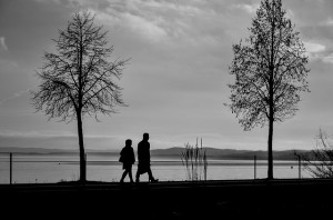 People walking near a lake discussing Alcoholism