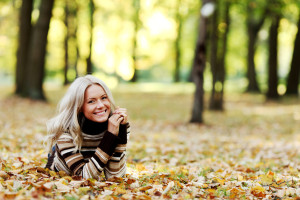 Woman Sitting In Leaves In The Park