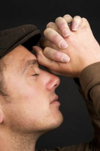 man praying with hands on head