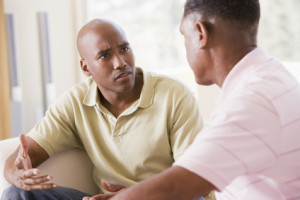 Two men in living room talking about Support Groups