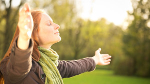 Woman worshiping with open arms or taking in the Autumn sun in a park.