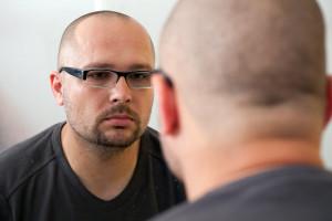 sad man in glasses looks in mirror