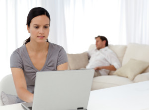 Attentive woman working on the laptop while her boyfriend is sle