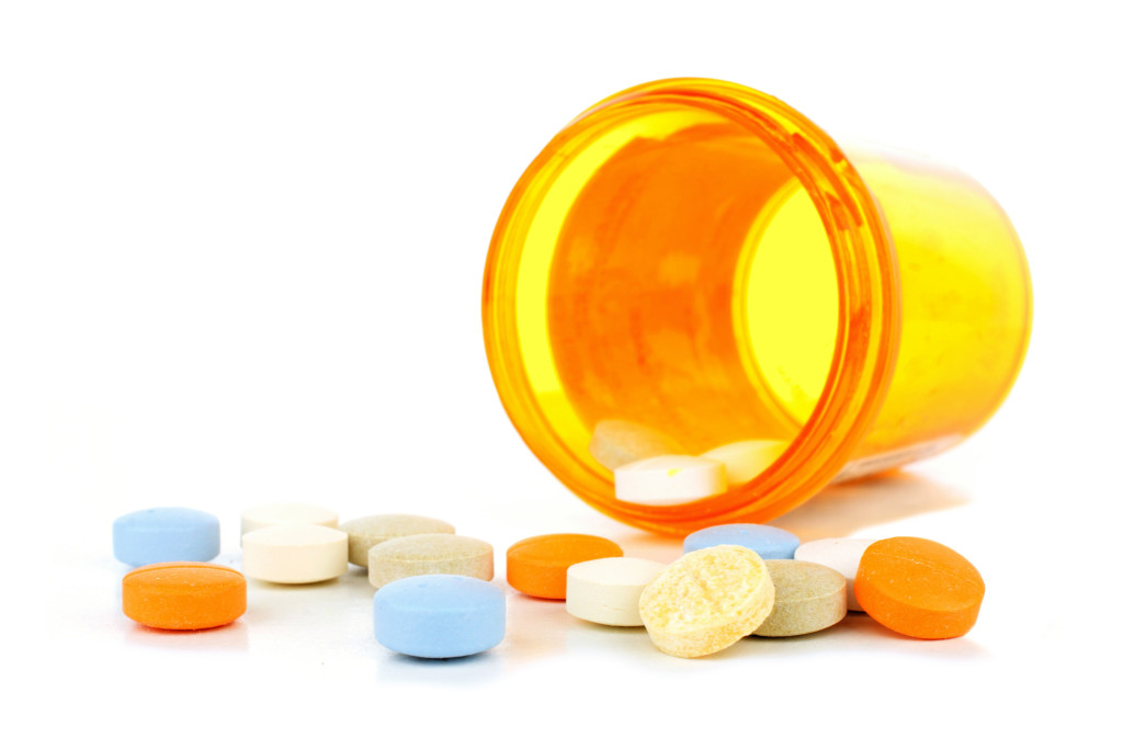 Pill bottle with spilling medicine tablets