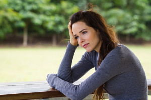 Sad depressed woman sitting outdoors after drinking Alcohol