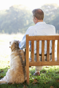 Senior man sitting outdoors with dog