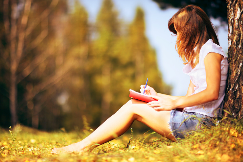 Young female student sitting near a tree and studying.