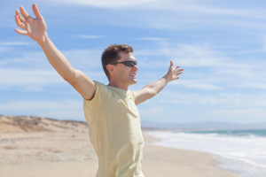young smiling man standing at the beach with arms wide open, freedom or happiness concept