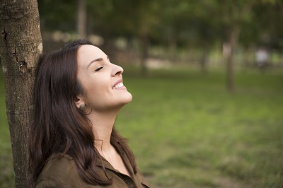Woman with happy expression relaxing on meadow