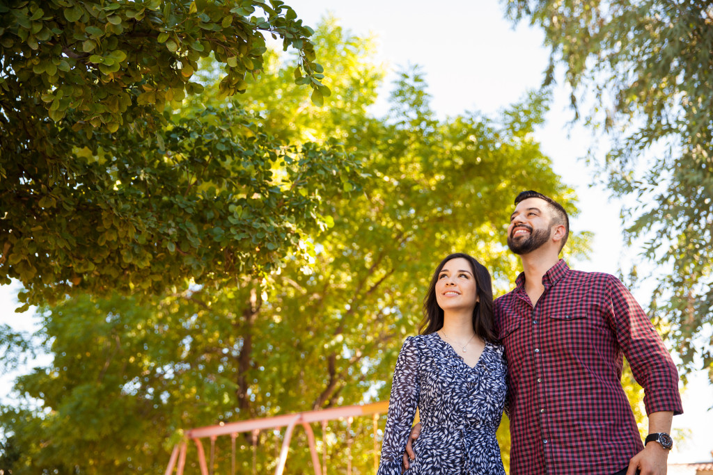 Portrait of a young couple hanging out at a park and looking up towards copy space