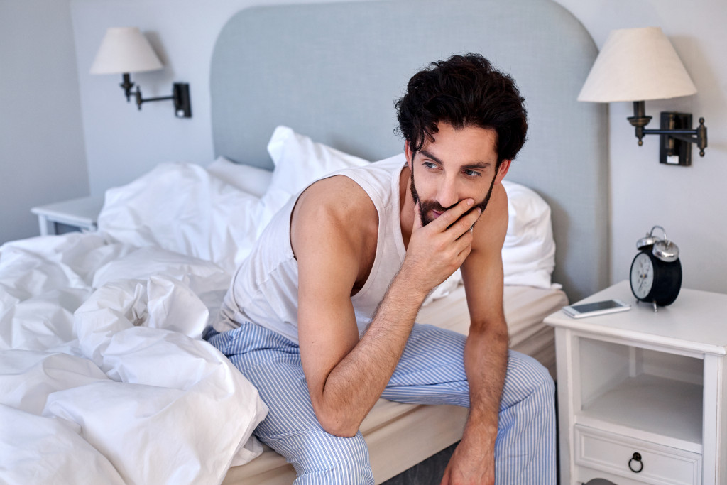 man with beard sitting on bed at home