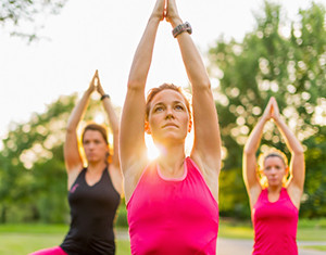 Group of 3 women doing yoga at sunset