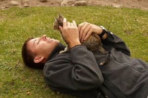 man laying on ground with cat