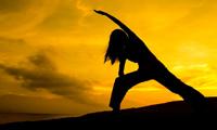Lady doing yoga in sunrise