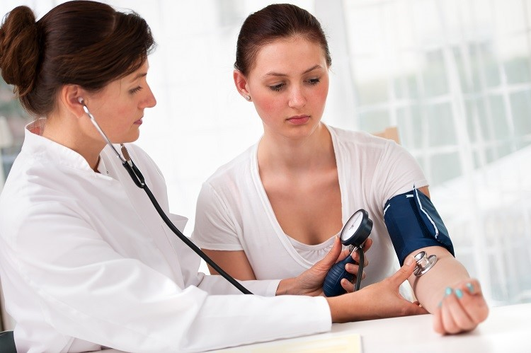 Female doctor checking young woman blood pressure