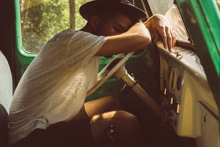 guy sleeping on truck steering wheel