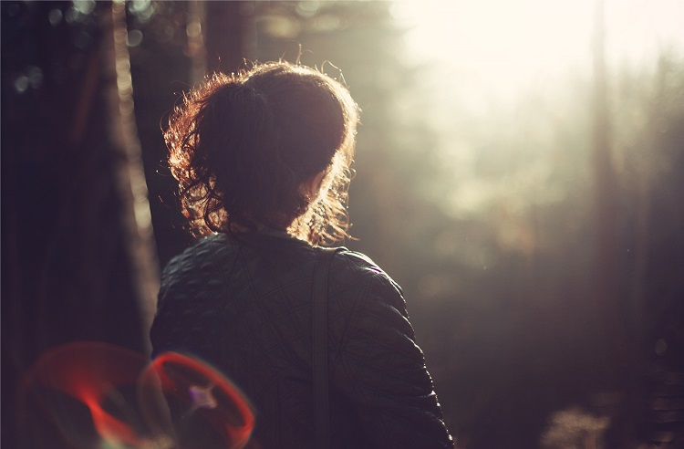 woman sitting in park at sunset
