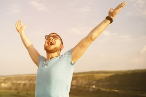 man yelling in joy with arms in air