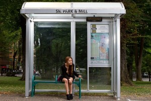young woman sitting at bus stop