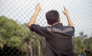 guy leaning on chain link fence