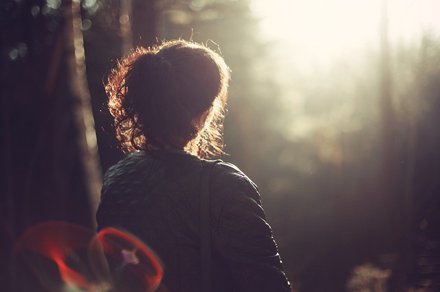 lady sitting in forest in sunset