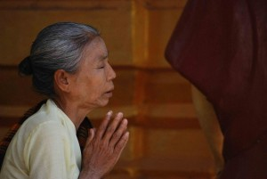 Older Indian woman kneeling and praying