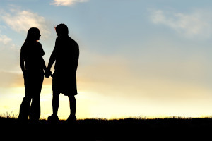 A silhouette of a happy young couple in a relationship, holding hands and talking as they walk outside at sunset.