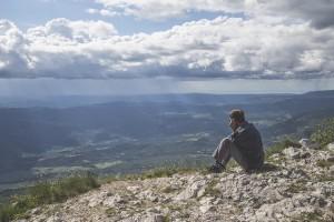 man sitting on top of mountaiin