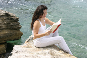 Lady sitting on edge of rock overlooking the ocean and reading a book