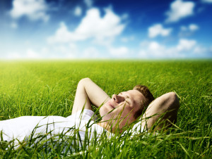young man laying in grassy field