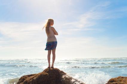girl on rock facing the sea
