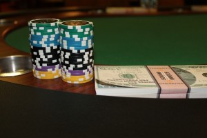 Poker chips and stack of cash on gaming table