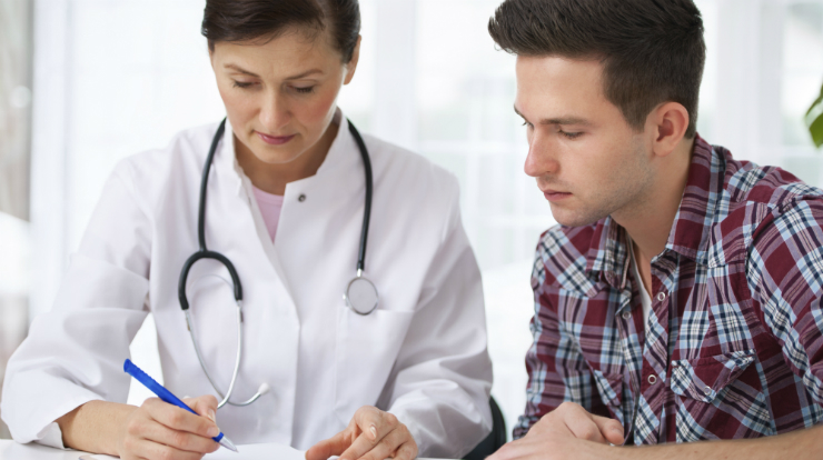 Doctor Writing Prescription For Young Man