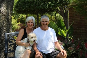 Older man with heart disease sitting with wife and dog.