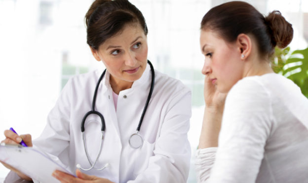 Female Doctor Working With Reluctant Woman