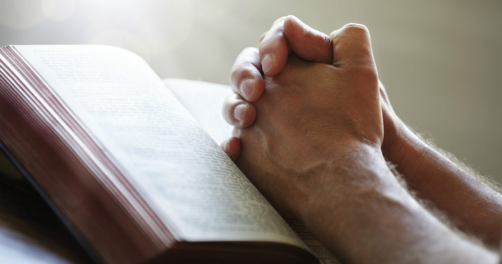 Man Praying and reading scripture