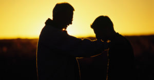 Man Praying Over Teenager - Addiction Hope