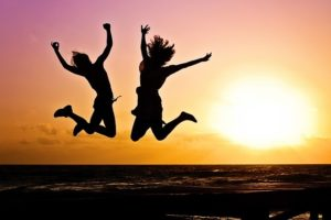 Two young adults leaping for joy