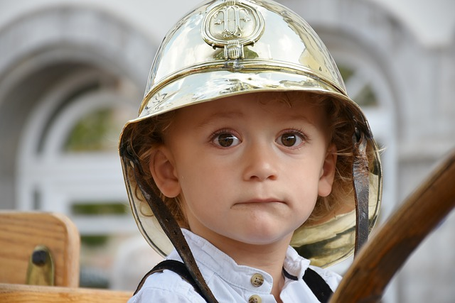 child struggling with self-injury being helped and wearing a fireman's helmet