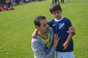 Young boy with his father at a soccer game