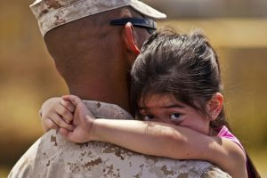 Father and young daughter hugging