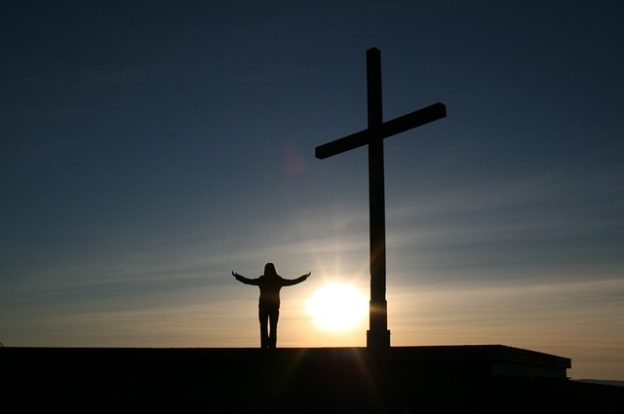 Man standing by a cross during sunset