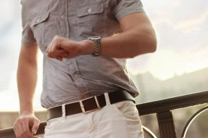 Man Looking At his Watch As He Runs Late