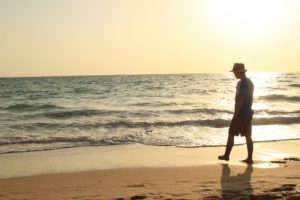 Man in addiction recovery walking on the beach
